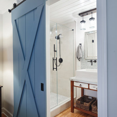 Inspiration for a country 3/4 glass tile medium tone wood floor and brown floor alcove shower remodel in Charlotte with furniture-like cabinets, brown cabinets, white walls, a vessel sink, a hinged shower door, marble countertops and white countertops
