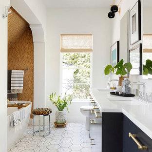 Diseño de cuarto de baño principal, ecléctico, con armarios con paneles lisos, puertas de armario negras, encimeras blancas, bañera exenta, baldosas y/o azulejos beige, paredes blancas, lavabo bajoencimera y suelo multicolor