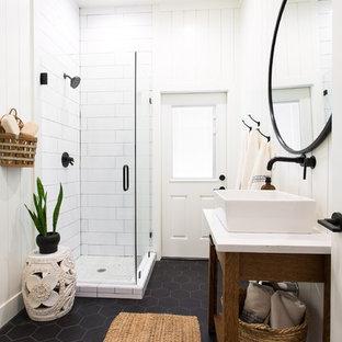 Klassisches Badezimmer mit verzierten Schränken, hellbraunen Holzschränken, Eckdusche, weißen Fliesen, weißer Wandfarbe, Aufsatzwaschbecken, schwarzem Boden, Falttür-Duschabtrennung und weißer Waschtischplatte in Sacramento