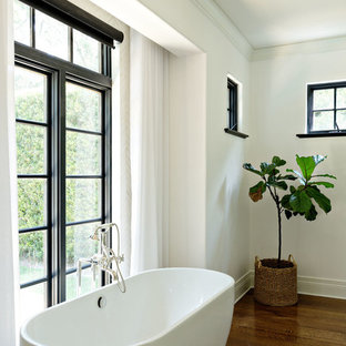 Example of a large tuscan master medium tone wood floor freestanding bathtub design in Orange County with shaker cabinets, white cabinets, white walls, a vessel sink and marble countertops