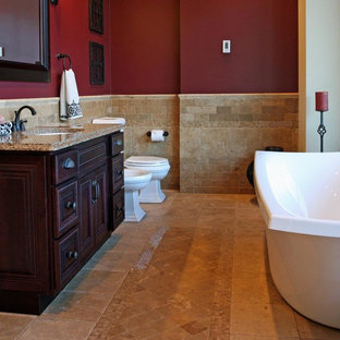 Idee per una stanza da bagno padronale mediterranea di medie dimensioni con lavabo sottopiano, ante con bugna sagomata, ante in legno bruno, top in quarzo composito, vasca freestanding, bidè, piastrelle beige, piastrelle in pietra, pareti rosse e pavimento in travertino