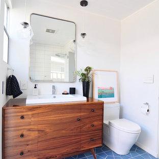 Immagine di una stanza da bagno padronale moderna con piastrelle bianche, piastrelle in ceramica, pareti bianche, pavimento con piastrelle in ceramica, pavimento blu, consolle stile comò, ante in legno scuro, WC monopezzo, lavabo da incasso, top in legno e top marrone