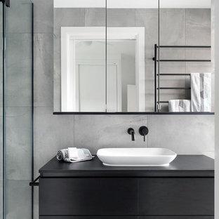 Пример оригинального дизайна: ванная комната в современном стиле с черными фасадами, цементной плиткой, серыми стенами, полом из цементной плитки, настольной раковиной, столешницей из ламината, серым полом, черной столешницей, плоскими фасадами, серой плиткой и душем с распашными дверями