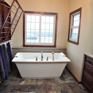 ブリッジポートの大きいトラディショナルスタイルのおしゃれなマスターバスルーム (レイズドパネル扉のキャビネット、中間色木目調キャビネット、置き型浴槽、アルコーブ型シャワー、分離型トイレ、ベージュのタイル、磁器タイル、オレンジの壁、磁器タイルの床、アンダーカウンター洗面器、珪岩の洗面台、マルチカラーの床、開き戸のシャワー) の写真