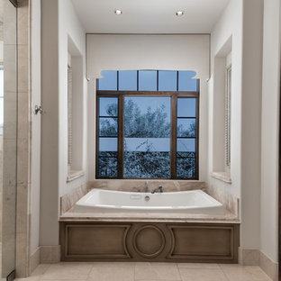 This is an example of an expansive mediterranean ensuite bathroom in Phoenix with raised-panel cabinets, dark wood cabinets, a built-in bath, an alcove shower, a one-piece toilet, multi-coloured tiles, mirror tiles, beige walls, porcelain flooring, a vessel sink, quartz worktops, multi-coloured floors, a hinged door and multi-coloured worktops.