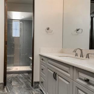 Expansive mediterranean ensuite bathroom in Phoenix with raised-panel cabinets, grey cabinets, a built-in bath, an alcove shower, a one-piece toilet, multi-coloured tiles, mirror tiles, beige walls, porcelain flooring, a vessel sink, quartz worktops, multi-coloured floors, a hinged door and multi-coloured worktops.
