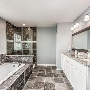 Diseño de cuarto de baño principal, tradicional renovado, grande, con armarios con paneles empotrados, puertas de armario blancas, bañera encastrada, ducha empotrada, sanitario de una pieza, baldosas y/o azulejos negros, paredes grises, lavabo bajoencimera, encimera de terrazo, suelo negro y ducha abierta