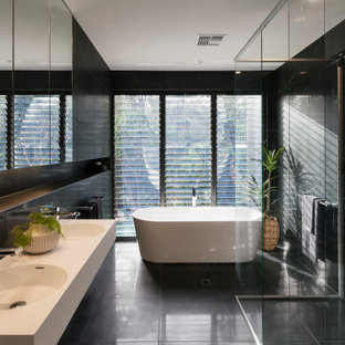Inspiration for a contemporary master bathroom in Sunshine Coast with open cabinets, white cabinets, a freestanding tub, a curbless shower, black tile, an integrated sink, black floor, an open shower, white benchtops, a double vanity and a floating vanity.