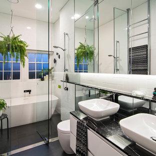 На фото: маленькая главная ванная комната в современном стиле с белыми фасадами, белой плиткой, белыми стенами, настольной раковиной, душем с распашными дверями, стеклянными фасадами, отдельно стоящей ванной, душевой комнатой, унитазом-моноблоком, плиткой кабанчик, полом из керамической плитки, мраморной столешницей, черным полом и черной столешницей с