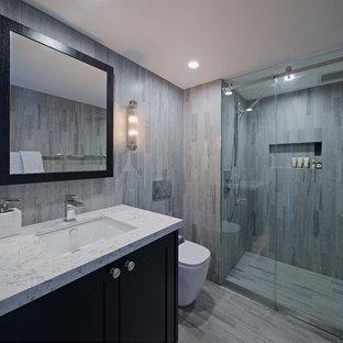 Ispirazione per una piccola stanza da bagno con doccia design con ante in stile shaker, ante nere, doccia alcova, WC monopezzo, piastrelle grigie, piastrelle in travertino, pareti grigie, pavimento in marmo, lavabo sottopiano, top in quarzo composito, pavimento grigio e porta doccia scorrevole