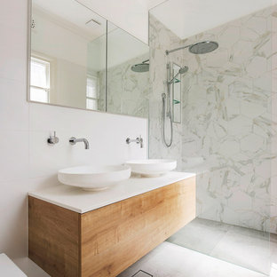 Design ideas for a contemporary bathroom in Sydney with flat-panel cabinets, medium wood cabinets, a curbless shower, a wall-mount toilet, white tile, white walls, a vessel sink, grey floor, an open shower and white benchtops.