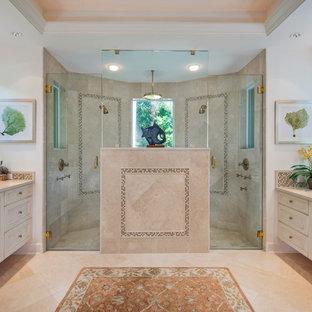 Inredning av ett klassiskt en-suite badrum, med ett undermonterad handfat, luckor med infälld panel, vita skåp, bänkskiva i kalksten, en dubbeldusch, beige kakel, porslinskakel, vita väggar och travertin golv