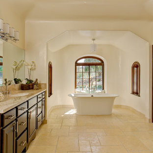 Inspiration for a large mediterranean ensuite bathroom in Los Angeles with a submerged sink, raised-panel cabinets, dark wood cabinets, marble worktops, a freestanding bath, beige tiles, beige walls, a walk-in shower, a two-piece toilet, travertine tiles, travertine flooring and beige floors.