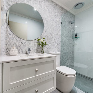 Design ideas for a small transitional 3/4 bathroom in Perth with shaker cabinets, white cabinets, a one-piece toilet, mosaic tile, porcelain floors, an undermount sink, solid surface benchtops, grey floor, an open shower, white benchtops, a curbless shower, gray tile and white walls.