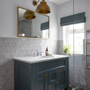 Design ideas for a small modern shower room bathroom in London with freestanding cabinets, blue cabinets, a walk-in shower, a wall mounted toilet, grey tiles, ceramic tiles, white walls, cement flooring, a built-in sink, marble worktops, grey floors, an open shower and white worktops.