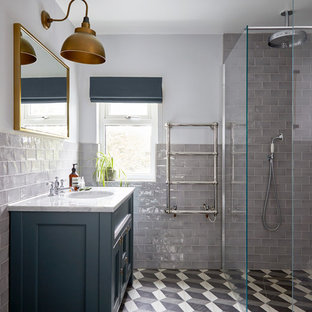 Inspiration for a small modern shower room in London with freestanding cabinets, blue cabinets, a walk-in shower, a wall mounted toilet, grey tiles, ceramic tiles, white walls, cement flooring, a built-in sink, marble worktops, grey floors, an open shower and white worktops.