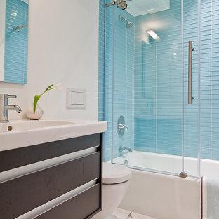 Foto di una stanza da bagno padronale design di medie dimensioni con vasca/doccia, WC sospeso, piastrelle blu, piastrelle di vetro, ante lisce, ante in legno bruno, vasca ad alcova, pareti bianche, pavimento in marmo, lavabo integrato e top in quarzo composito