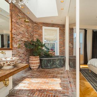 Modelo de cuarto de baño con ducha, de estilo de casa de campo, con bañera exenta, ducha a ras de suelo, paredes blancas, suelo de ladrillo, lavabo sobreencimera, encimera de madera, suelo marrón, ducha abierta y encimeras marrones