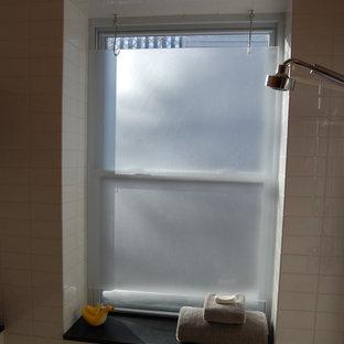 Immagine di una stanza da bagno con doccia minimal di medie dimensioni con ante lisce, ante bianche, vasca sottopiano, doccia alcova, WC monopezzo, piastrelle bianche, piastrelle in gres porcellanato, pareti arancioni, lavabo integrato e top in quarzo composito