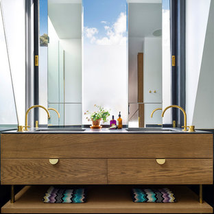 This is an example of a contemporary bathroom in Sydney with flat-panel cabinets, dark wood cabinets, white walls, an integrated sink and black floor.