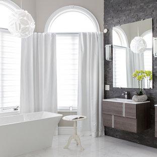 Idées déco pour une grande salle de bain principale classique avec un placard à porte plane, des portes de placard en bois sombre, une baignoire indépendante, un mur beige et un lavabo encastré.
