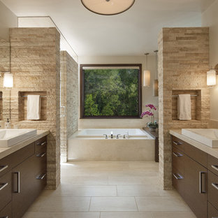 Imagen de cuarto de baño principal, actual, con lavabo sobreencimera, armarios con paneles lisos, puertas de armario de madera en tonos medios, encimera de mármol, suelo de travertino, bañera encastrada, baldosas y/o azulejos beige, paredes beige y baldosas y/o azulejos de travertino