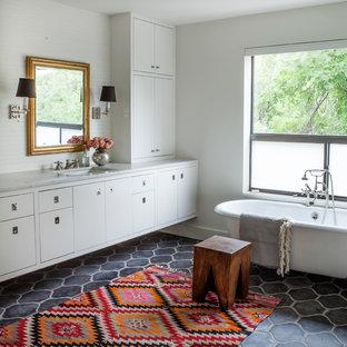 Modelo de cuarto de baño clásico renovado con lavabo bajoencimera, armarios con paneles lisos, puertas de armario blancas, bañera con patas, baldosas y/o azulejos blancos y paredes blancas