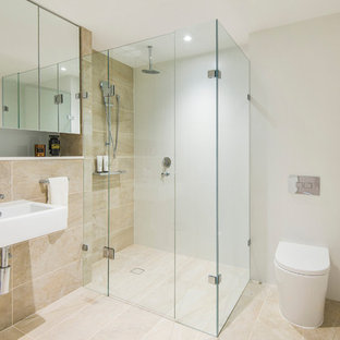 This is an example of a small contemporary 3/4 bathroom in Sydney with a corner shower, a one-piece toilet, beige tile, marble, white walls, marble floors, a wall-mount sink, beige floor, a hinged shower door and flat-panel cabinets.