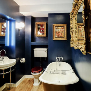 Diseño de cuarto de baño infantil, clásico, pequeño, con armarios tipo mueble, puertas de armario de madera oscura, bañera con patas, sanitario de dos piezas, paredes azules, suelo de madera clara y lavabo tipo consola
