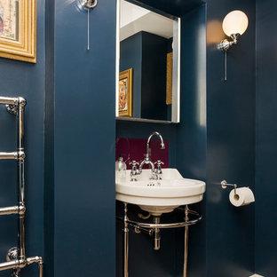 Idee per una piccola stanza da bagno per bambini bohémian con consolle stile comò, ante in legno scuro, vasca con piedi a zampa di leone, WC a due pezzi, pareti blu, parquet chiaro e lavabo a colonna