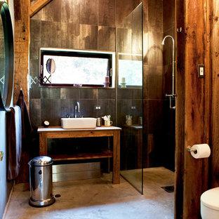 Diseño de cuarto de baño rústico, de tamaño medio, con lavabo sobreencimera, baldosas y/o azulejos de porcelana, suelo de cemento, armarios abiertos, puertas de armario de madera oscura, ducha empotrada, paredes marrones, suelo marrón y ducha con puerta con bisagras