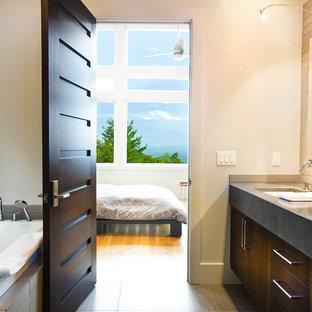 Modelo de cuarto de baño contemporáneo con lavabo bajoencimera, armarios con paneles lisos, puertas de armario de madera en tonos medios, bañera encastrada y baldosas y/o azulejos grises