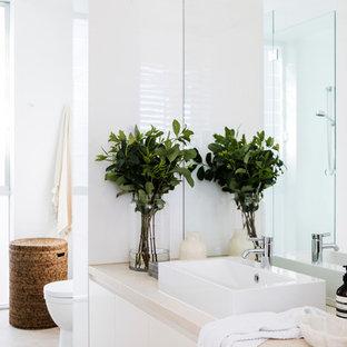Idee per una stanza da bagno padronale stile marinaro di medie dimensioni con ante lisce, ante bianche, piastrelle bianche, lastra di pietra, pareti bianche, pavimento con piastrelle in ceramica, lavabo a bacinella, pavimento beige e top beige