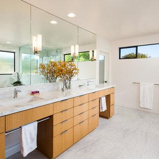 Inredning av ett modernt stort en-suite badrum, med ett undermonterad handfat, släta luckor, skåp i ljust trä, vit kakel, ett undermonterat badkar, en hörndusch, en toalettstol med separat cisternkåpa, marmorkakel, vita väggar, marmorgolv, marmorbänkskiva, vitt golv och dusch med gångjärnsdörr