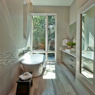 Modernes Badezimmer mit freistehender Badewanne, Aufsatzwaschbecken, beigefarbenen Fliesen und Steinfliesen in Austin