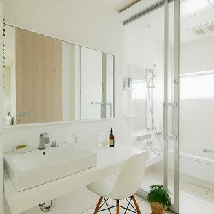 Modelo de cuarto de baño actual, sin sin inodoro, con paredes blancas, lavabo sobreencimera, armarios tipo vitrina, bañera empotrada, baldosas y/o azulejos blancos, suelo blanco y ducha abierta