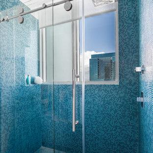 Diseño de cuarto de baño infantil, moderno, de tamaño medio, con armarios con paneles lisos, puertas de armario blancas, ducha empotrada, sanitario de una pieza, baldosas y/o azulejos azules, baldosas y/o azulejos en mosaico, paredes blancas, lavabo sobreencimera y encimera de acrílico
