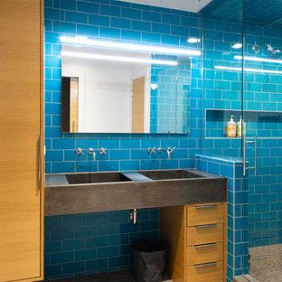 Mittelgroßes Modernes Kinderbad mit flächenbündigen Schrankfronten, blauen Fliesen, blauer Wandfarbe, Porzellan-Bodenfliesen, integriertem Waschbecken, Beton-Waschbecken/Waschtisch, Falttür-Duschabtrennung, grauer Waschtischplatte, hellbraunen Holzschränken, Duschnische, Metrofliesen und beigem Boden in Omaha