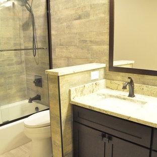 Foto di una piccola stanza da bagno industriale con lavabo sottopiano, ante in stile shaker, ante in legno bruno, top in granito, vasca sottopiano, vasca/doccia, WC a due pezzi, piastrelle marroni, piastrelle in ceramica e pavimento con piastrelle in ceramica