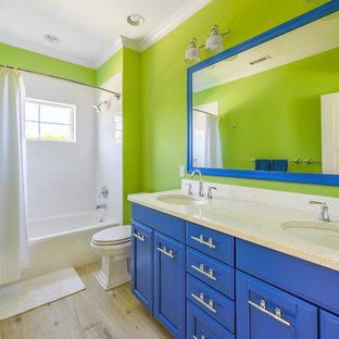 Bild på ett maritimt badrum, med släta luckor, blå skåp, gröna väggar och dusch med duschdraperi