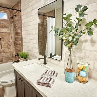 Diseño de cuarto de baño infantil, rústico, de tamaño medio, con armarios estilo shaker, puertas de armario con efecto envejecido, bañera empotrada, ducha empotrada, sanitario de una pieza, baldosas y/o azulejos blancos, baldosas y/o azulejos de cemento, paredes blancas, suelo de baldosas de porcelana, lavabo bajoencimera, encimera de cuarzo compacto, suelo marrón, ducha con cortina y encimeras blancas