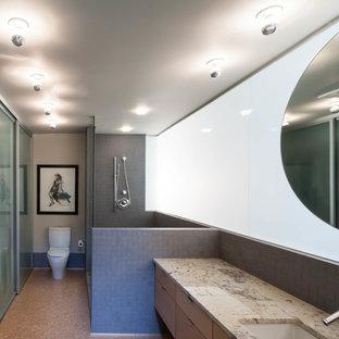 Immagine di una stanza da bagno padronale design di medie dimensioni con lavabo da incasso, ante lisce, ante in legno chiaro, top in granito, doccia aperta, WC monopezzo, piastrelle grigie, piastrelle in gres porcellanato, pareti bianche e pavimento in sughero