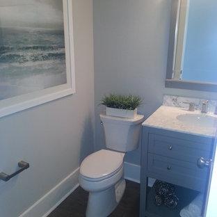 Ispirazione per una piccola stanza da bagno con doccia stile marinaro con lavabo sottopiano, consolle stile comò, ante grigie, top in marmo, WC a due pezzi, piastrelle bianche, pareti grigie e pavimento in legno massello medio