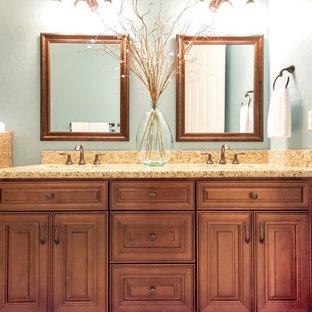 フェニックスの中くらいのトランジショナルスタイルのおしゃれな子供用バスルーム (茶色いキャビネット、ドロップイン型浴槽、シャワー付き浴槽、ベージュのタイル、磁器タイル、青い壁、磁器タイルの床、アンダーカウンター洗面器、御影石の洗面台、レイズドパネル扉のキャビネット、分離型トイレ、ベージュの床、開き戸のシャワー) の写真