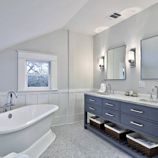 This is an example of a medium sized traditional ensuite bathroom in Austin with a freestanding bath, marble worktops, grey tiles, blue cabinets and flat-panel cabinets.