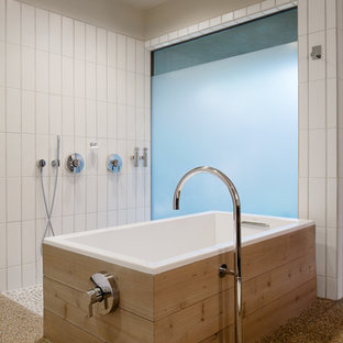 Retro bathroom in Austin with pebble tile flooring, a freestanding bath, white tiles, beige walls and a built-in shower.
