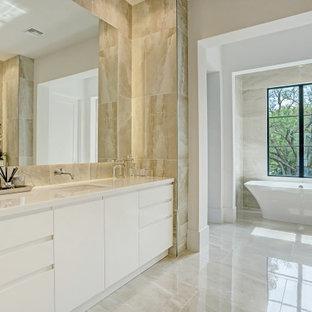 Modern inredning av ett stort vit vitt en-suite badrum, med släta luckor, vita skåp, ett fristående badkar, beige kakel, vita väggar, ett undermonterad handfat och beiget golv