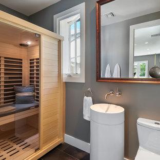 Ispirazione per una piccola sauna minimalista con ante a persiana, ante in legno chiaro, WC monopezzo, pareti grigie, pavimento in gres porcellanato, lavabo a colonna e pavimento marrone