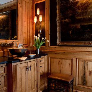 Ejemplo de cuarto de baño con ducha, rústico, de tamaño medio, con lavabo sobreencimera, armarios con paneles empotrados, puertas de armario de madera oscura, suelo de madera oscura, paredes negras y encimera de cuarzo compacto