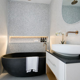 Inspiration for a contemporary bathroom in Sydney with flat-panel cabinets, white cabinets, a freestanding tub, an open shower, gray tile, ceramic tile, grey walls, ceramic floors, a vessel sink, engineered quartz benchtops, black benchtops, grey floor and an open shower.